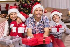 在长沙发提供的礼物的欢乐的家庭 免版税图库摄影