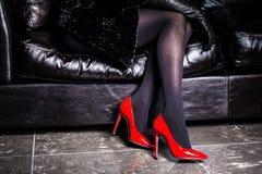 在长沙发有脚跟的妇女腿指向隔绝的 免版税库存图片