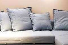 在长沙发正面图的软的灰色枕头,特写镜头 免版税库存图片
