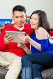 在长沙发的亚洲夫妇有片剂个人计算机的 库存照片