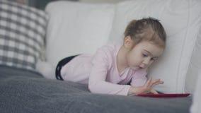 在长沙发的使变冷的小女孩冲浪的片剂 股票录像