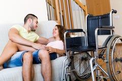 在长沙发的夫妇在轮椅附近 库存照片