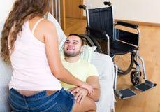 在长沙发的夫妇在轮椅附近 库存图片