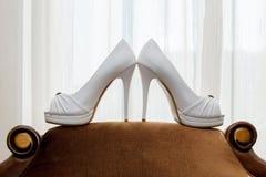 在长沙发的女傧相鞋子 库存照片