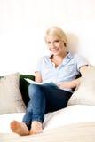 在长沙发的女性开会读一本书 库存图片