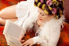 在长沙发的妇女读书 库存照片