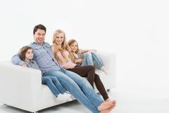 在长沙发的家庭 免版税库存照片