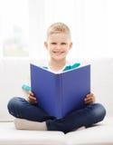 在长沙发的微笑的小男孩阅读书 免版税库存照片