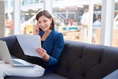 在长沙发的微笑的busineswoman有电话、膝上型计算机和文书工作的 库存照片