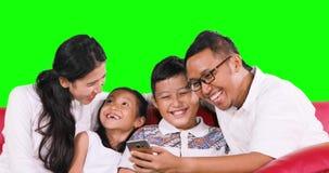 在长沙发的快乐的家庭用途智能手机 影视素材
