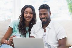 在长沙发的愉快的夫妇使用膝上型计算机 免版税库存图片