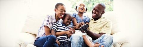 在长沙发的愉快的微笑的家庭 库存图片
