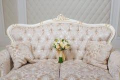 在长沙发的新娘花束 库存照片