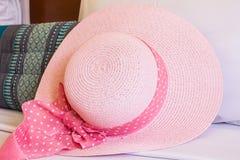 在长沙发的桃红色帽子 免版税图库摄影