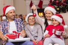 戴在长沙发的欢乐的家庭圣诞老人帽子 库存图片