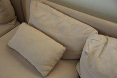 在长沙发的灰色棕色织品枕头 库存图片