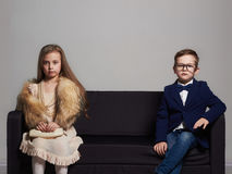 在长沙发的美好的夫妇 秀丽小女孩和男孩 开玩笑时髦 图库摄影