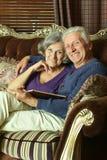 在长沙发的资深夫妇 免版税库存图片