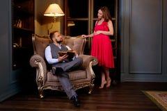 在长沙发的年轻夫妇阅读书在家 库存照片