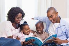 在长沙发读书故事书的愉快的家庭 免版税库存照片