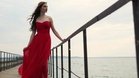 在长的丝绸礼服穿戴的亭亭玉立的时装模特儿在一个码头摆在自白天 影视素材