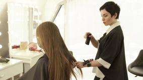 在长的头发女性理发的美发师喷洒的水在理发沙龙 在美容院的女性发型 影视素材