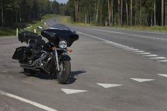 在长的旅途上的黑摩托车 路过路 免版税库存照片