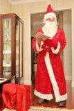 读在长的明亮的衣服的圣诞老人一封信在屋子里在与礼物的大红色袋子旁边,不摆在,自然照片-俄罗斯, M 免版税图库摄影