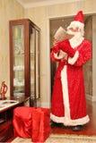 读在长的明亮的衣服的圣诞老人一封信在屋子里在与礼物的大红色袋子旁边,不摆在,自然照片-俄罗斯, M 免版税库存图片