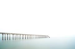 在长的曝光和白色天空,消极空间的渔跳船 免版税图库摄影