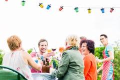 在长的桌上庆祝党的朋友和邻居 免版税图库摄影