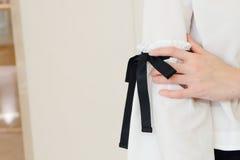 在长的白色袖子的妇女手有黑串蝶形领结样式细节的 关闭时髦时尚 免版税库存照片