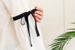 在长的白色袖子的妇女手有黑串蝶形领结样式细节的 关闭时髦时尚 库存图片