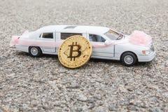 在长的白色豪华汽车附近模型的金黄硬币Bitcoin特写镜头在沥青背景的 免版税库存图片