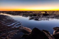 在长的礁石海滩的岩石在黎明 库存图片