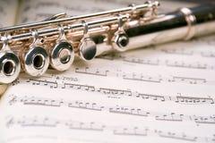 在长笛乐谱间 免版税库存图片