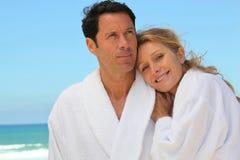 在长袍的夫妇在海滩 免版税库存图片