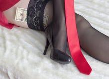 在长袜金钱伴游的女性腿 免版税库存照片