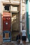 在门前面选址的古老妇女在从La哈瓦那,古巴的一个老房子里 库存照片