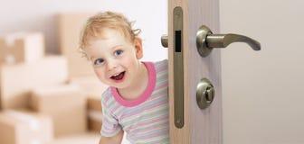 在门后的愉快的孩子在新的屋子里 免版税图库摄影