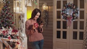 在门廊的妇女微笑的饮料茶用途电话与在背景的圣诞树 股票录像