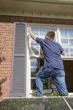 在门画家绘画修整视窗附近 免版税图库摄影