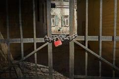 在门的红色锁对后院 库存照片