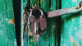 在门的老葡萄酒铁锁与被剥皮的绿色油漆 当钥匙伸出在它看法的关闭 股票录像