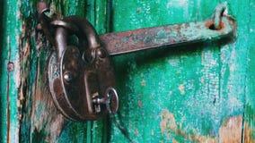 在门的老葡萄酒铁锁与被剥皮的绿色油漆 当钥匙伸出在它看法的关闭 股票视频
