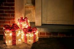 在门道入口的被点燃的装饰的圣诞节礼物盒 免版税库存照片