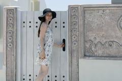 在门附近的一个少妇对在圣托里尼海岛上的公寓  免版税图库摄影