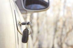 在门,一个模糊的秋天森林的背景的被忘记的汽车钥匙有bokeh作用的 库存照片