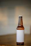 在门廊桌上的空白的标签啤酒瓶 库存图片