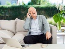 在门廊的快乐的老人回答的智能手机 免版税图库摄影